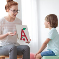 Young boy sitting on mint chair focusing on speech lessons with friendly speech therapist